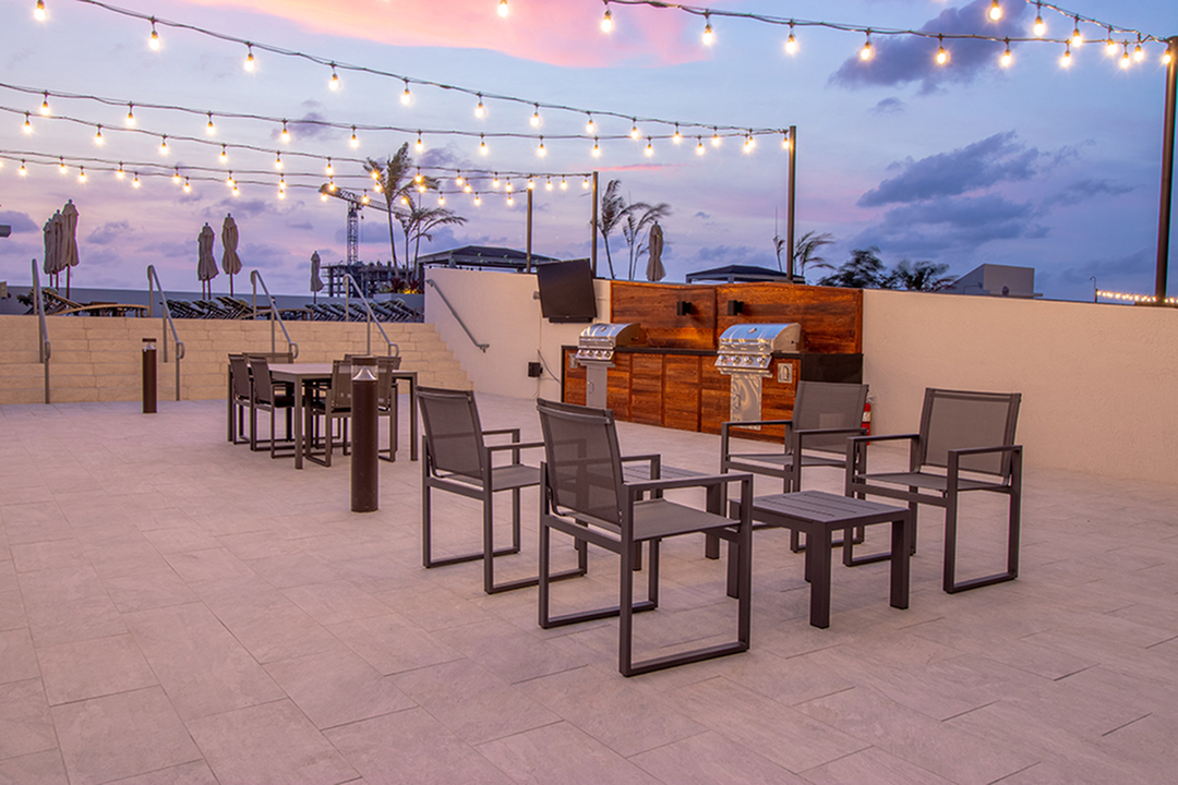 Roof top grilling area with social seating and string lights