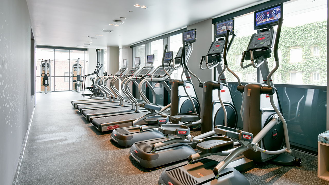Fitness center with cardio equipment facing floor to ceiling windows