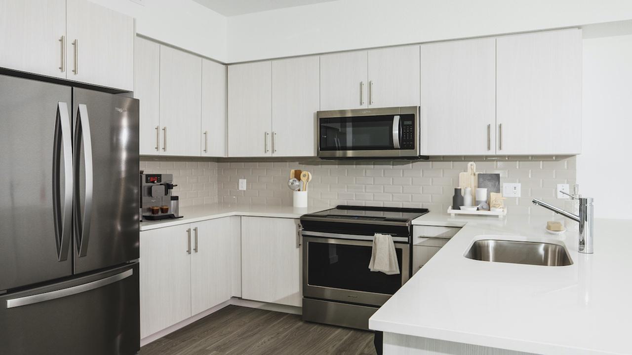 Kitchen with white cabinetry custom backsplash, and ample storage