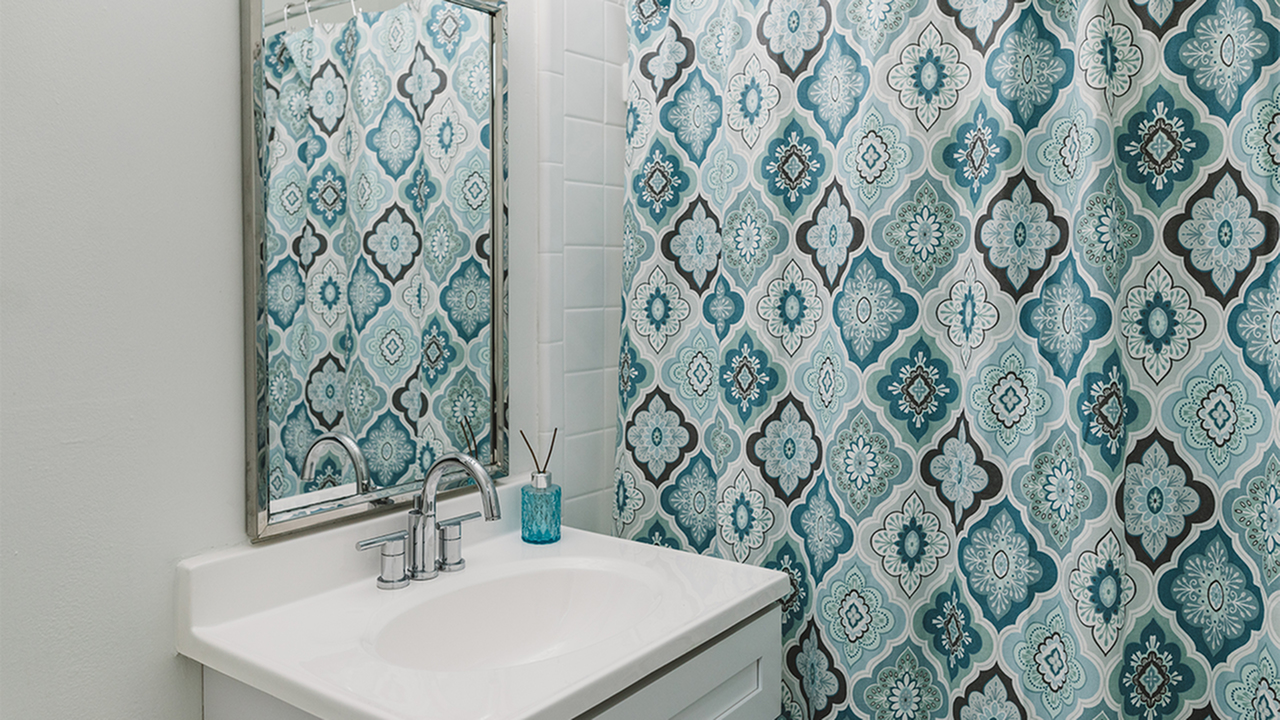 Bathroom sink next to tub with blue patterned shower curtain