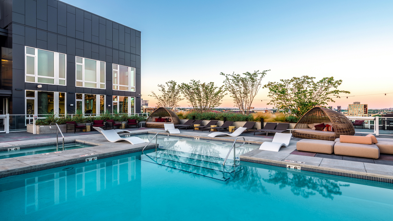 Pool with resort-inspired lounge seating and private cabanas