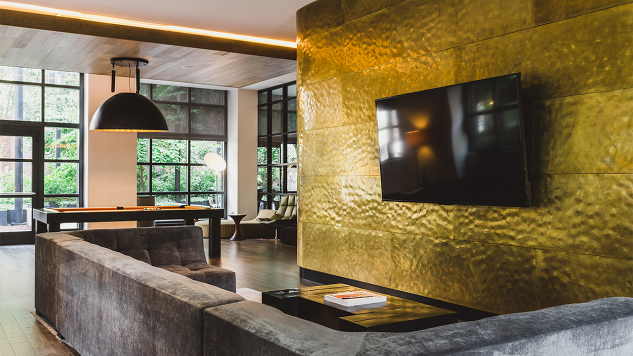 TV lounge with flatscreen on gold wall and a pool table