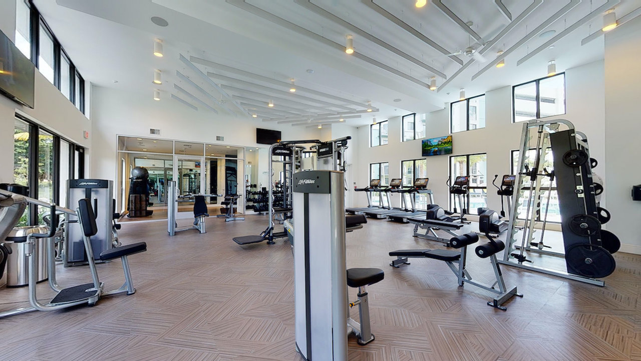 Large fitness center with weight stations, treadmills, ellipticals, and private yoga lounge