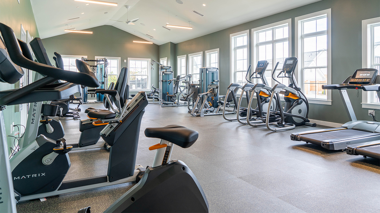 Expansive fitness center with spin bikes and weight stations