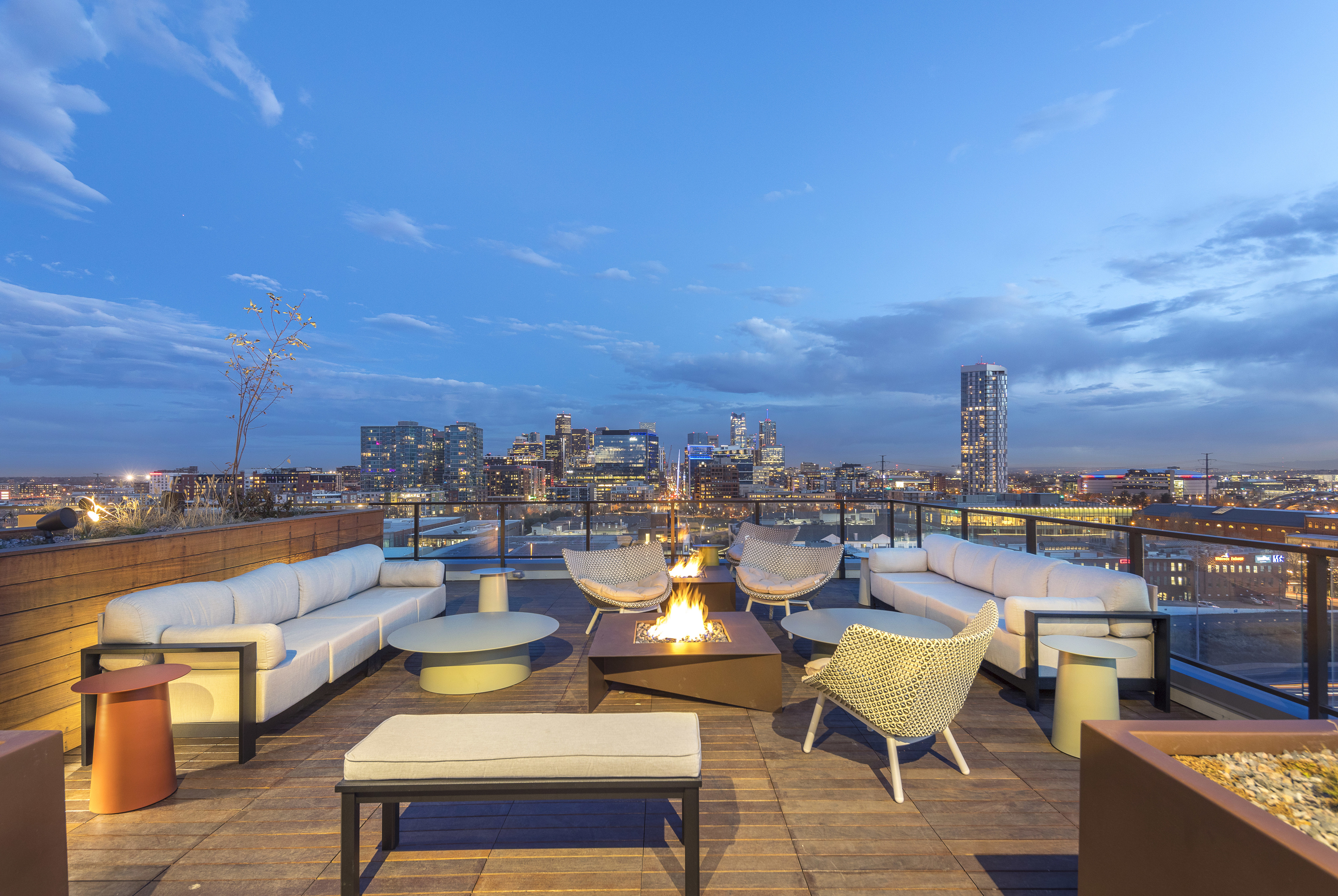 Private rooftop deck with lush landscaping, fire pits, outdoor tv, green space, and modern lounge seating to enjoy city and mountain views