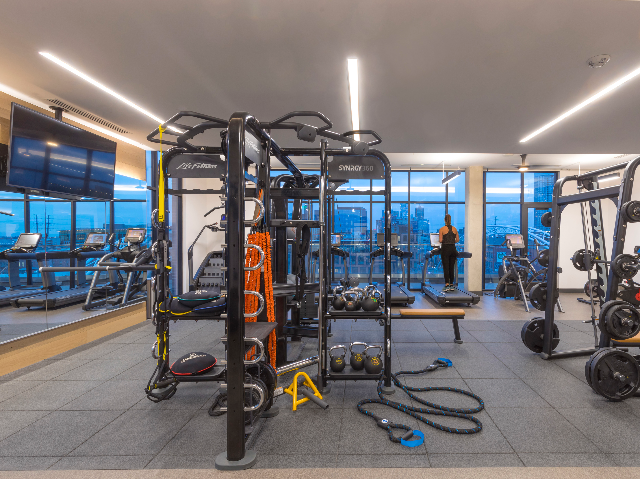HIIT inspired fitness center featuring TRX equipment, weight machines, and city views