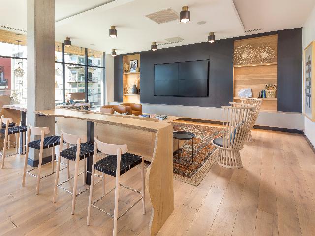 WiFi lounge with large flatscreen TV, coffee bar, and rustic modern decor