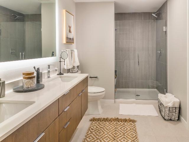 Tile bathroom floors with floor-to-ceiling tile shower, floating bathroom vanity, and frameless glass doors