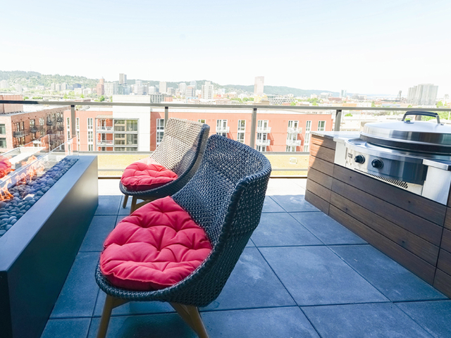Grilling station and glass-walled fire pit with fire roaring on rooftop terrace