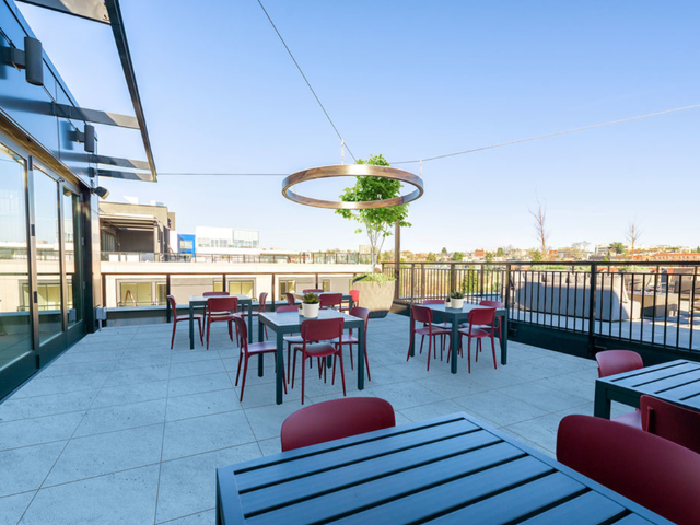 Rooftop resident lounge space with multiple tables and stylish lighting