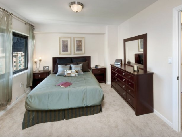 Furnished bedroom with wall-to-wall carpeting