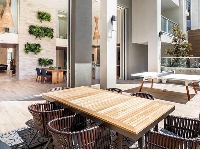 Outdoor tables next to a ping pong table that connects to an airy two-story indoor-outdoor courtyard with dramatic lighting