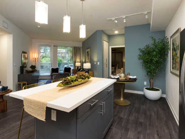 Large kitchen island with dedicated dining area in the background a large fridge in the foreground