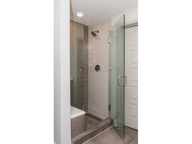 Walk-in glass showers with tile and bench seating