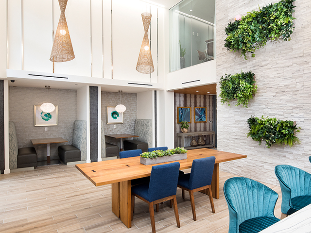 Open indoor lounge with elegant co-working spaces and coworking areas with a green wall feature