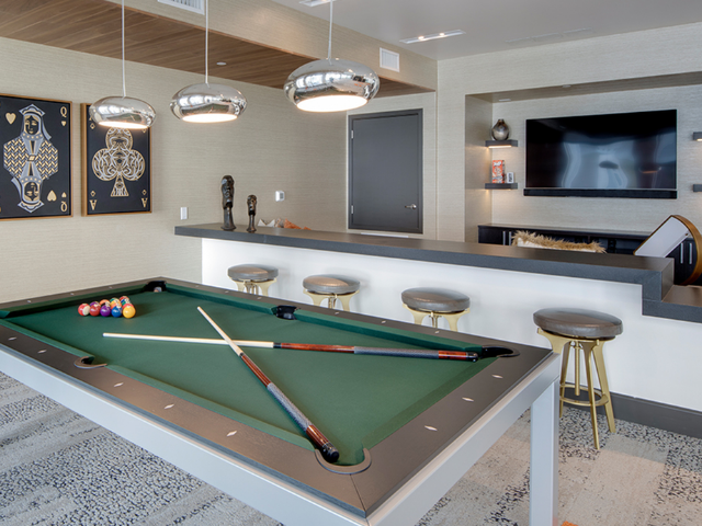 Billiards table behind a living area with TV