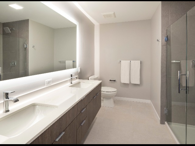 Bathroom at Modera LoHi showing gray and white color scheme and flooring