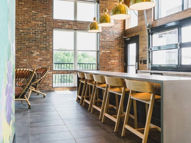 Long waterfall island with barstool chairs in a light-filled space facing garage door that opens to the outdoors