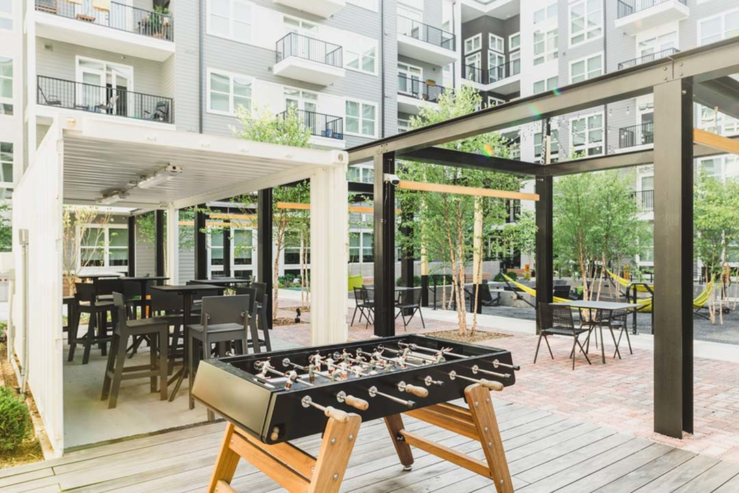 Unique outdoor space featuring hanging chairs and paved courtyard with social seating