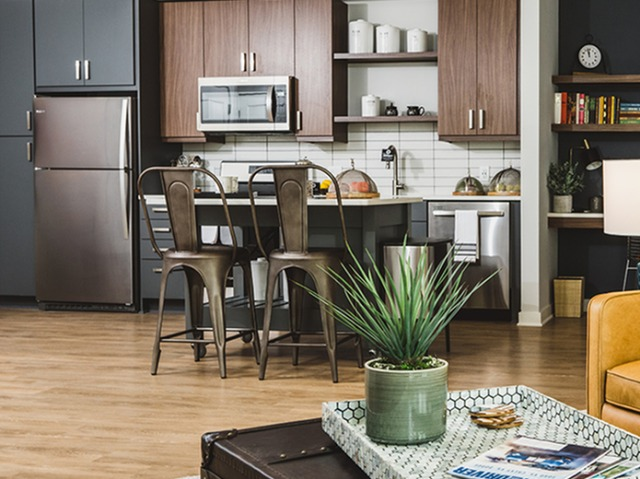 Two-tone kitchen with open shelving, island, and wood-plank style flooring