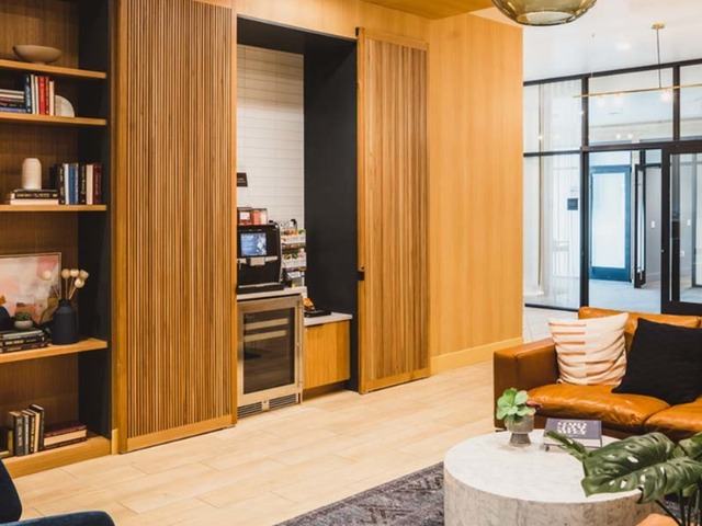 Coffee station in plush lounge with couches and library shelving in the lobby area