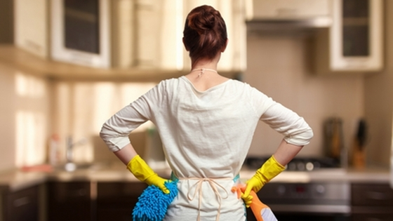A woman with yellow gloves and cleaning supplies.