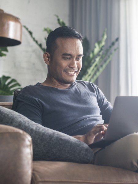 Man relaxing at home on laptop