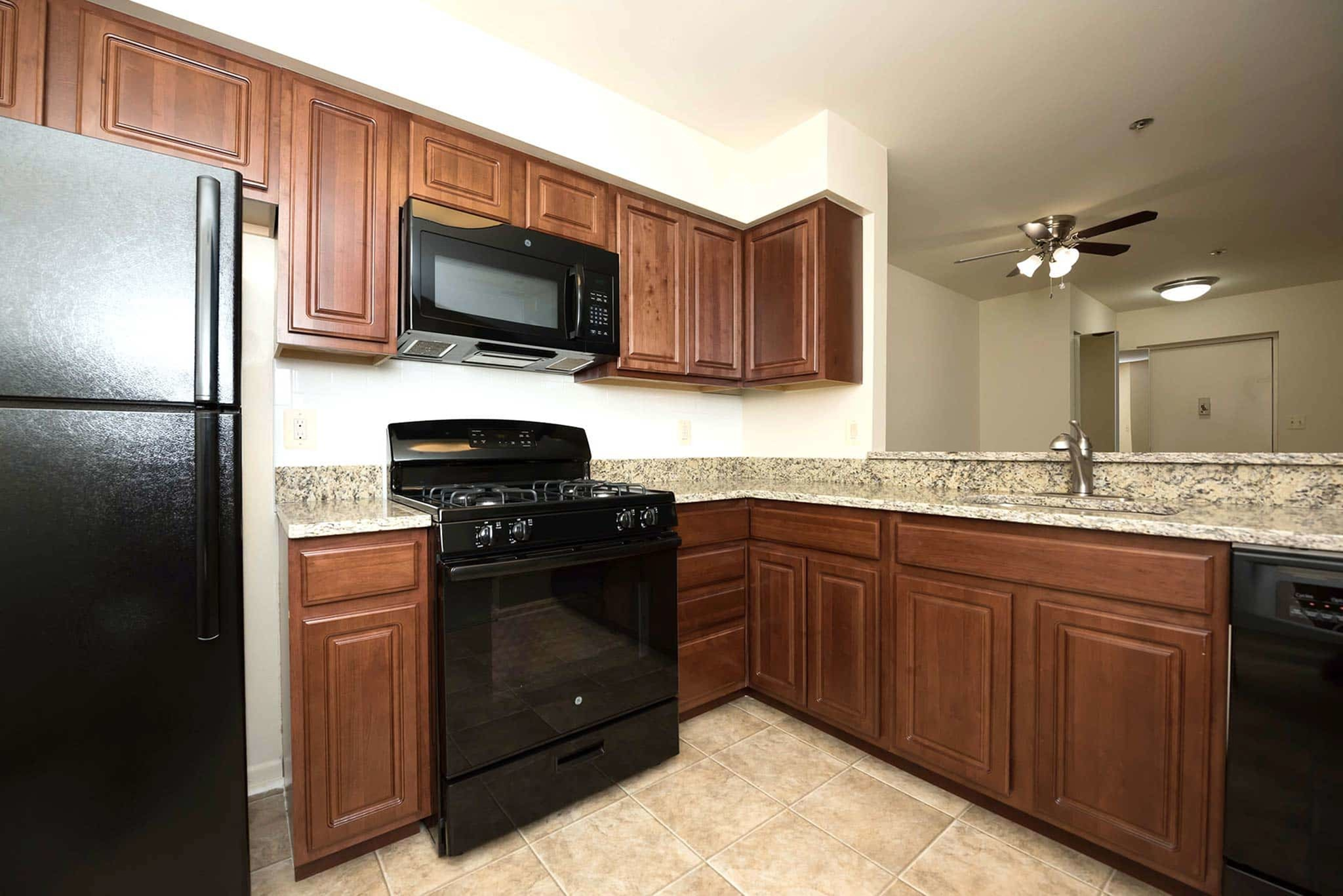 Beautiful kitchen with dark wooden cabinets and hard floors in Yorkshire Apartments in Silver Spring, MD