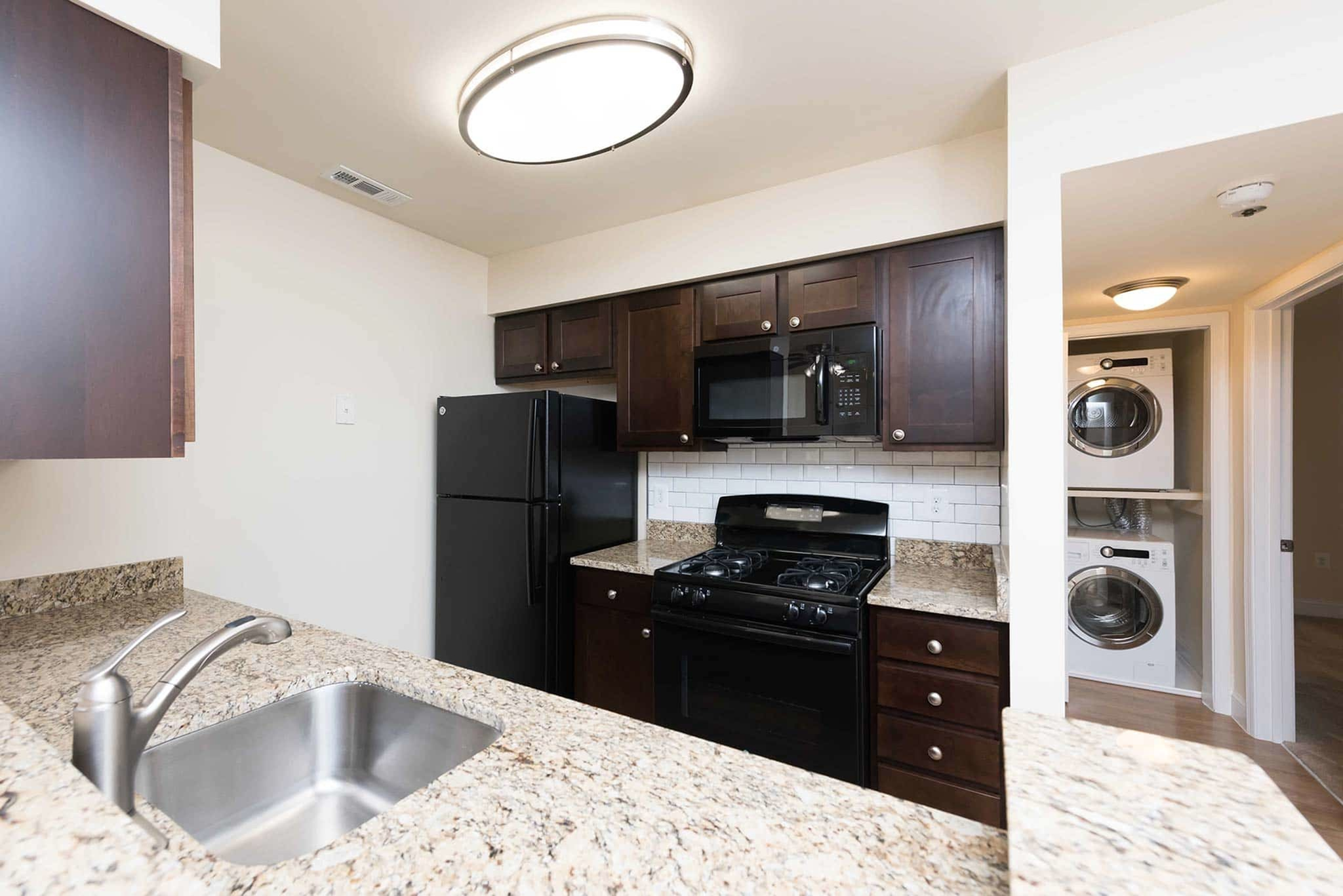 Gorgeous kitchen with dark wooden cabinets and marble sink decks in Yorkshire Apartments in Silver Spring, MD