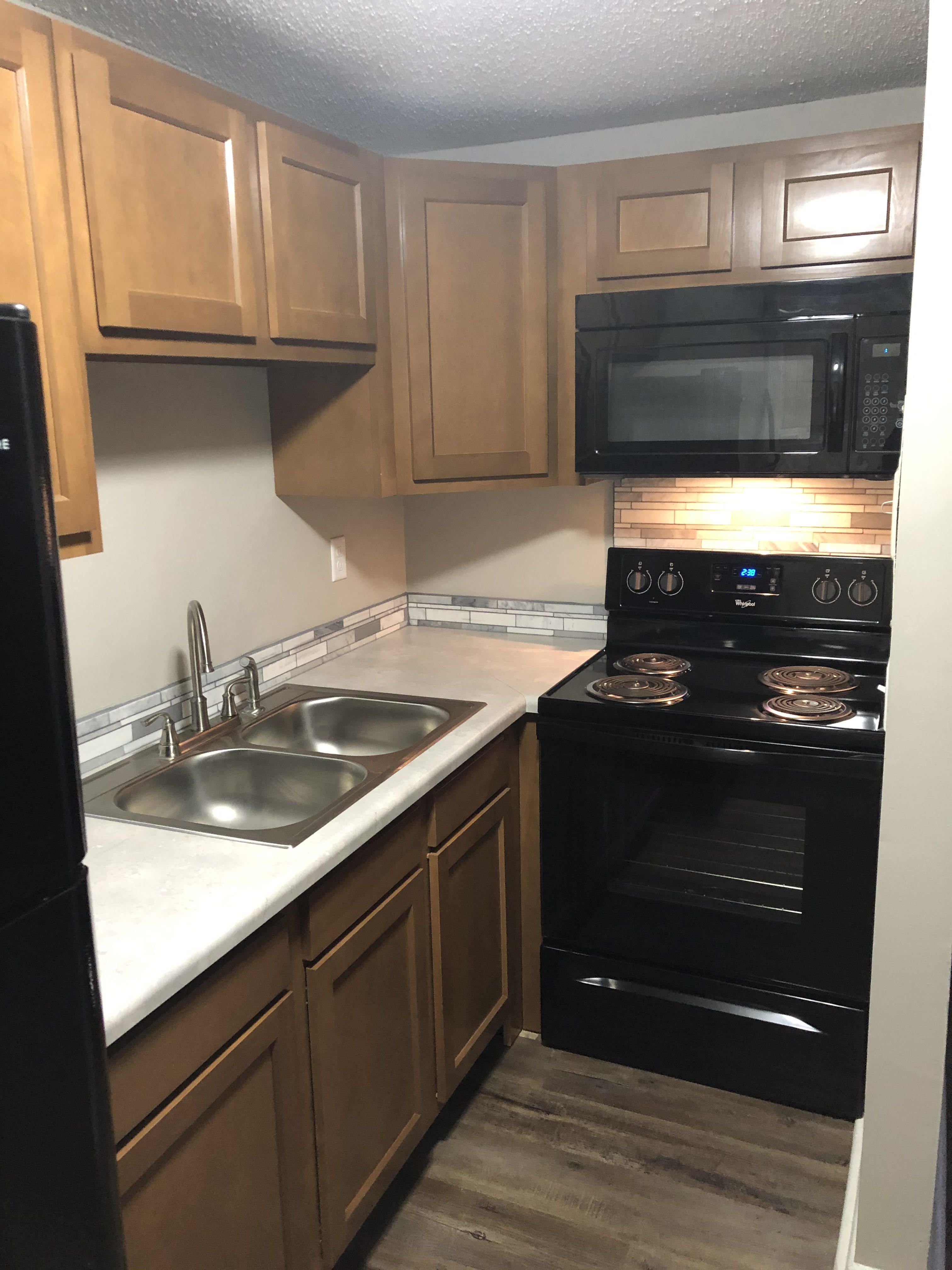 Newly renovated kitchen with black appliances and light brown cabinets