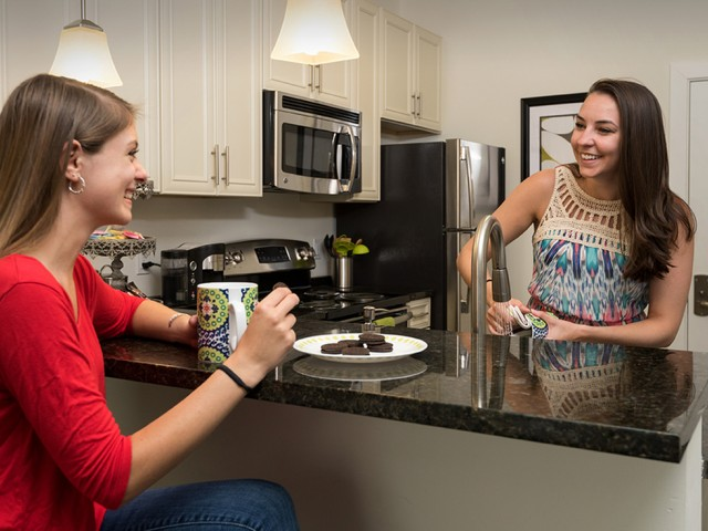 two girls eating in kitchen