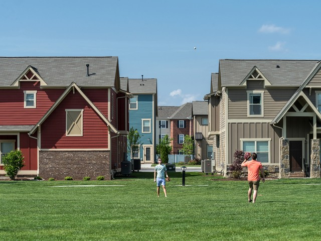 two residents playing catch in the plentiful green space on community grounds