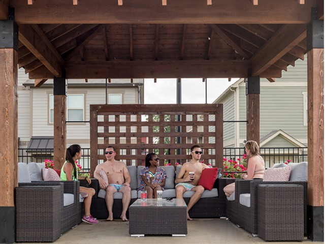 residents utilizing the lounge seating in a poolside cabana