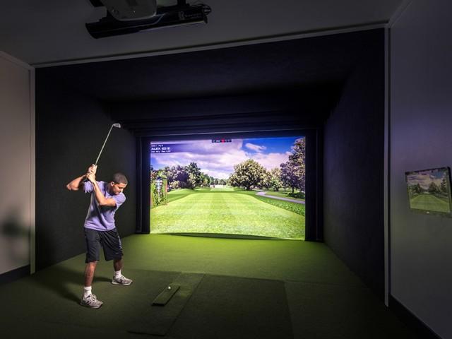 resident using the community golf simulator