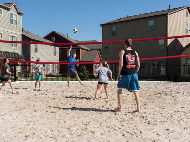 residents playing volleyball outside in the sand volleyball court