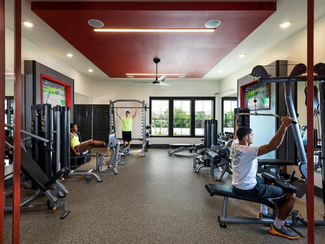 residents utilizing the fitness center equipped with resistance machines and free weights