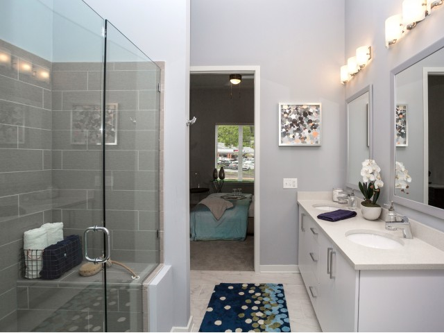 Image of Unwind in the luxurious master bath featuring a walk-in shower and gleaming marble-style tile. for Aston City Springs
