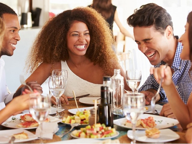 Friends laughing during meal
