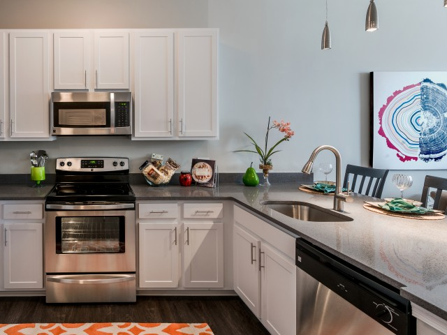 Kitchen with white shaker cabinets and grey granite counters