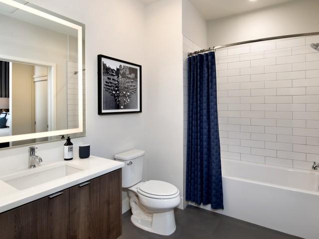 White tile bathroom with wood floors