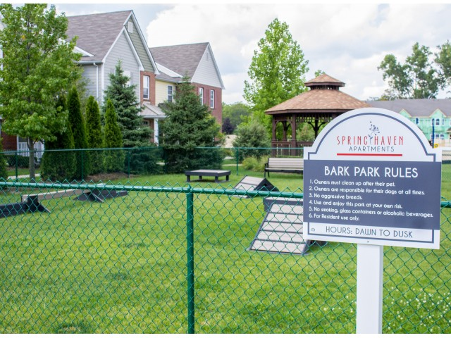 Bark Park fenced in with green grass and some obstacles the animals can use. Green trees surrounding the area with a gazebo in front of the building.