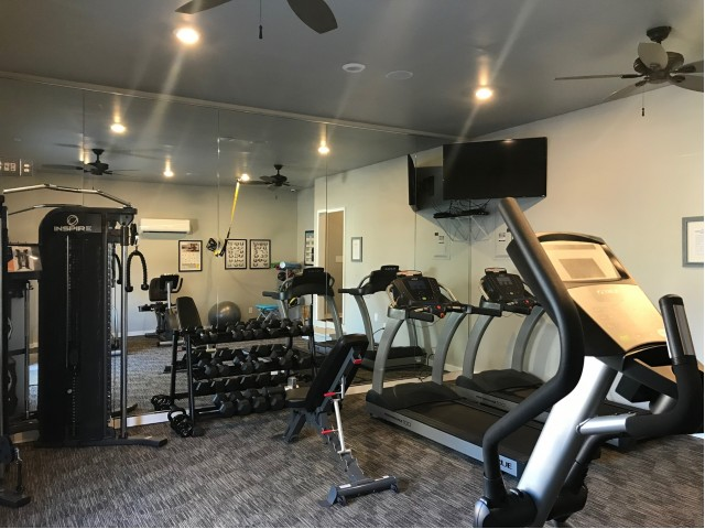 Gym with one wall all mirror, two treadmills, a weight rack, TV in the corner with two ceiling fans. Carpeted area