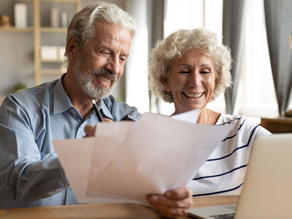 Senior couple reviewing papers at a table