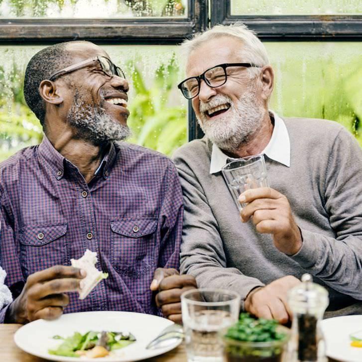 two senior men joking and laughing together overture senior living