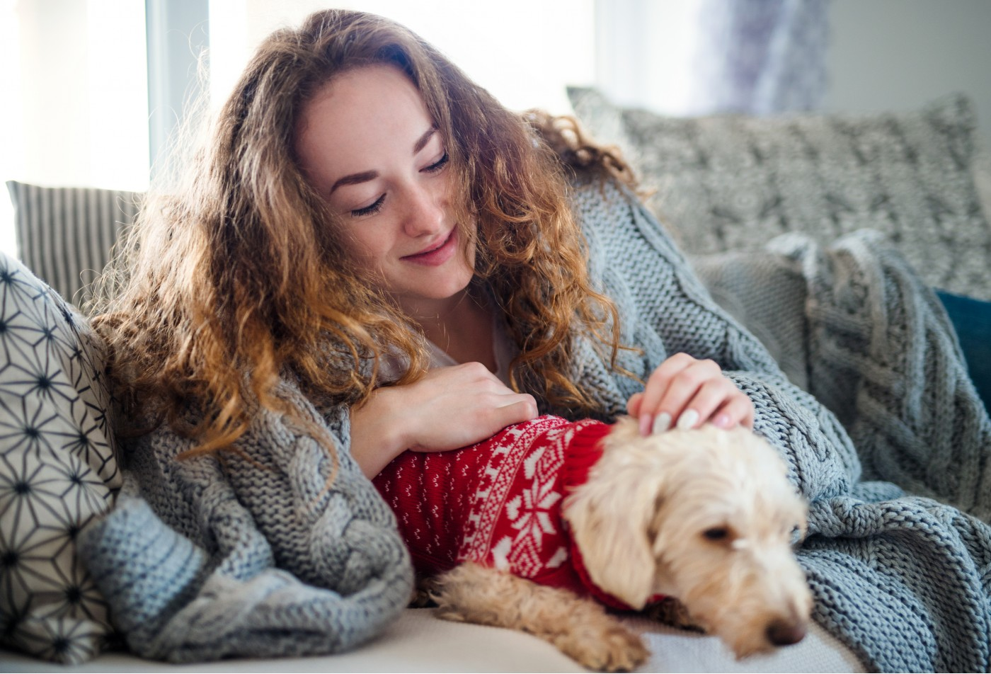 Young woman relaxing indoors on sofa at home with pet dog