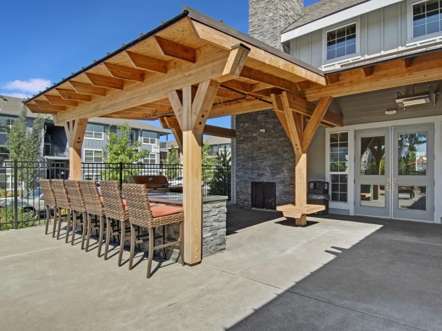 Image of Outdoor Gas BBQ and Dining Area with Park Benches for Seasons Apartments at Farmington Reserve
