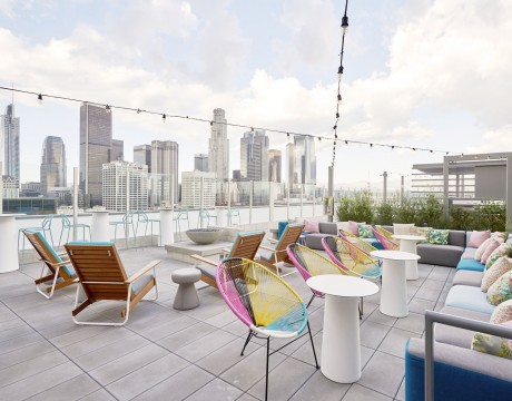 Rooftop patio at The Grace on Spring. There are chairs, tables, lighting overhead, and a view of Los Angeles skyline.