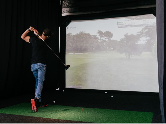 someone swinging a golf club in front of a virtual simulation