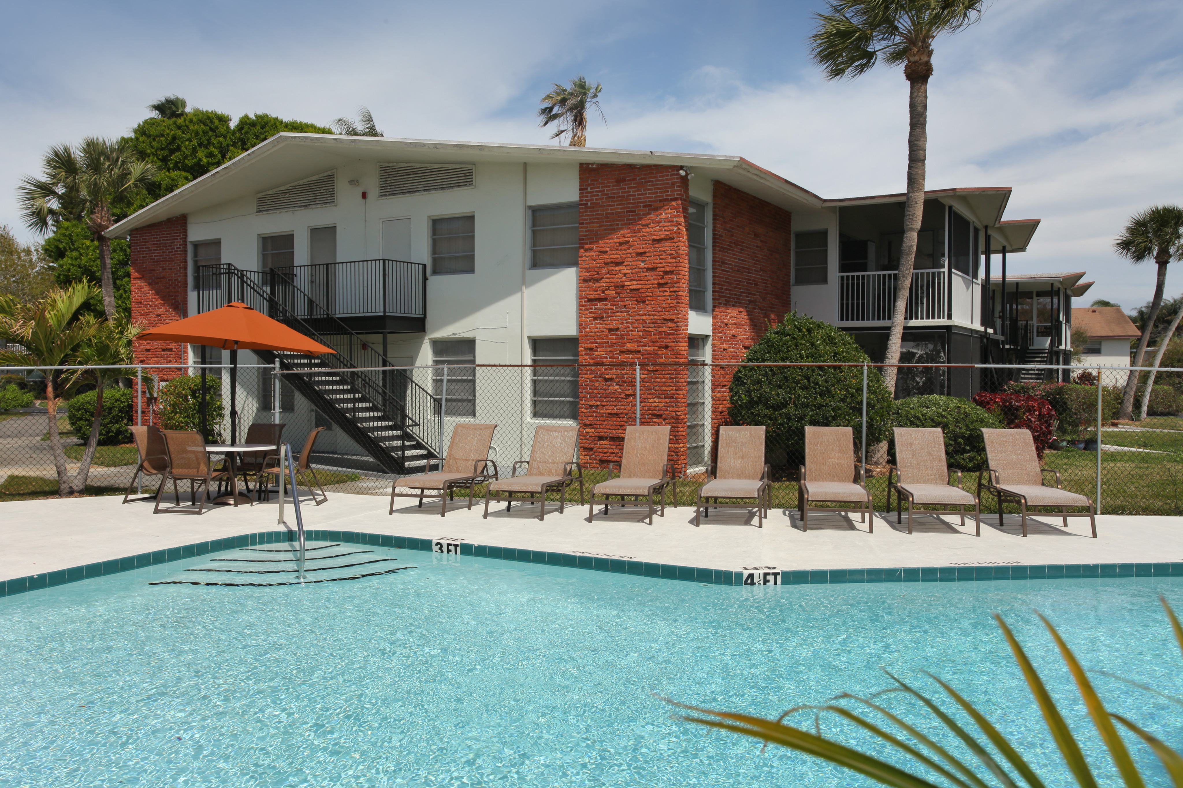Photo of community swimming pool area with outdoor seating and umbrellas, with apartment building in background.