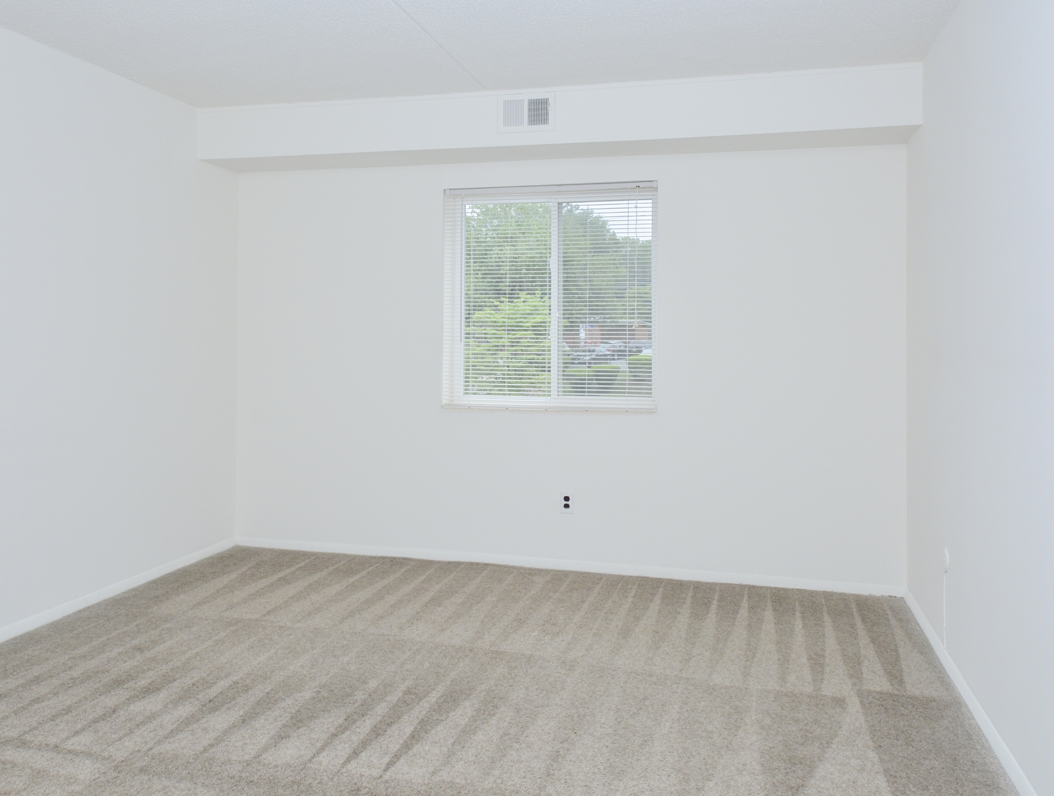 Gladstone Towers Sample Bedroom with Beige Carpet and Window | Apartments in Lansdowne PA